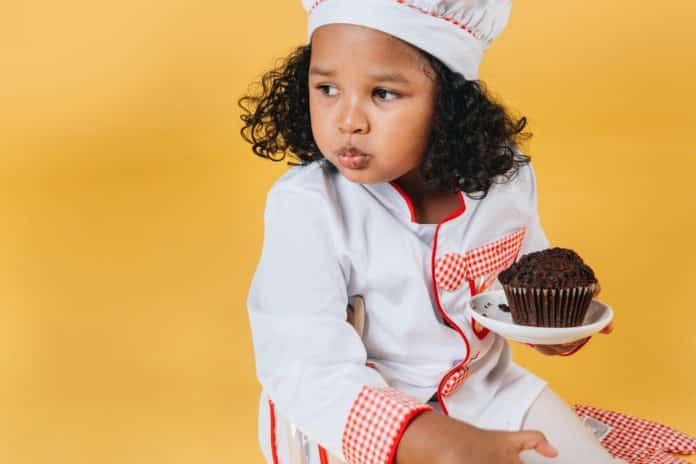 cute black girl chewing sweet baked dessert